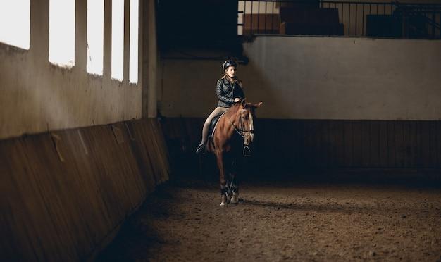 Jeune femme faisant de l'équitation en manège intérieur