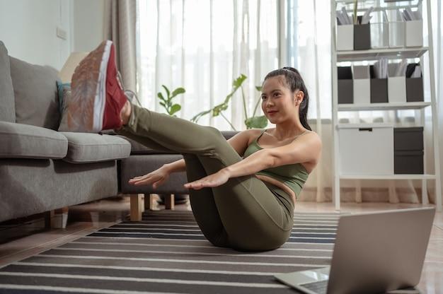 Jeune femme faisant de l'exercice à la maison dans un salonjeune femme répétant des exercices d'entraînement en ligne