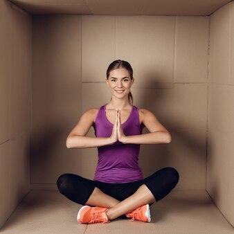 Jeune femme faisant des exercices dans une boîte en carton.