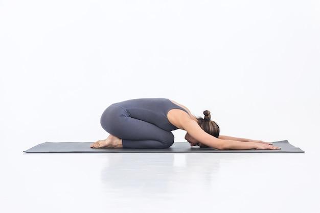 Jeune femme faisant des exercices à l'intérieur allongée sur un tapis dans une position de détente