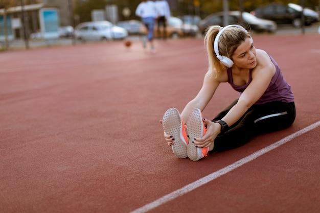 Jeune femme faisant des exercices et des jambes tendues à la cour en plein air