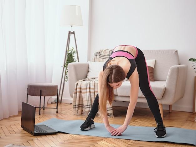 Jeune femme faisant des exercices à la maison. élongation