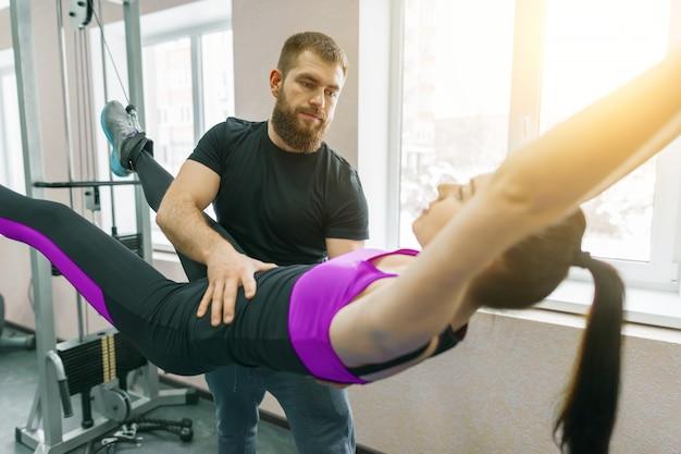 Jeune femme faisant des exercices de rééducation avec un instructeur personnel