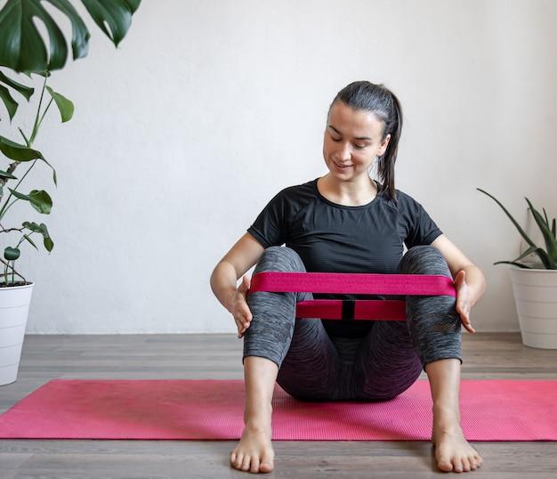 Jeune femme faisant des exercices de sport avec bande élastique à la maison sur le tapis, fitness à la maison, étirements et yoga.