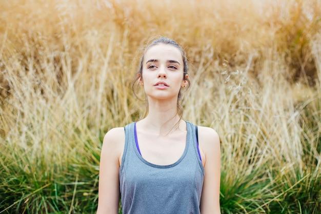 Jeune femme faisant des exercices de yoga dans un parc verdoyant
