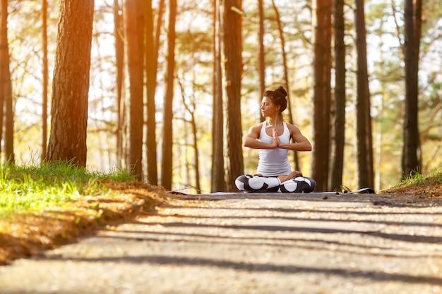 Jeune femme faisant des exercices de yoga dans le parc de la ville en automne. concept de mode de vie de santé.