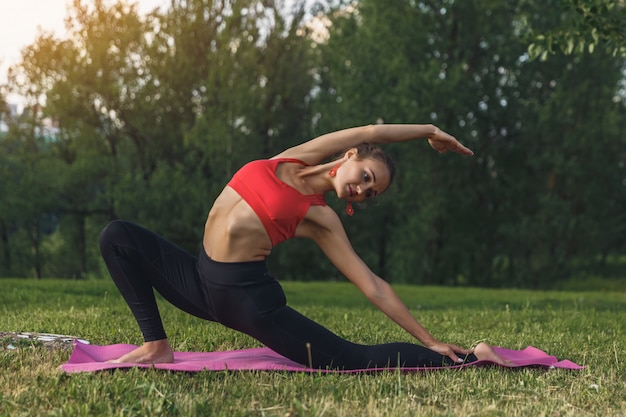 Jeune femme faisant des exercices de yoga dans le parc de la ville d'été