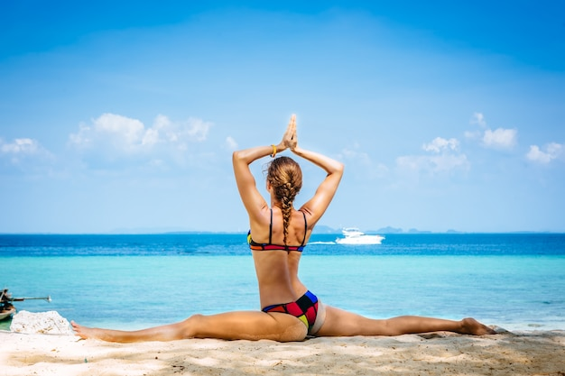 Jeune femme faisant des exercices de yoga sur la plage de la mer