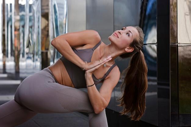 Jeune femme faisant des exercices de yoga avec la ville sur fond.