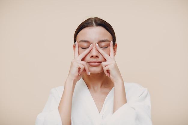 Jeune femme faisant face à l'auto-massage de gymnastique faciale et des exercices de rajeunissement