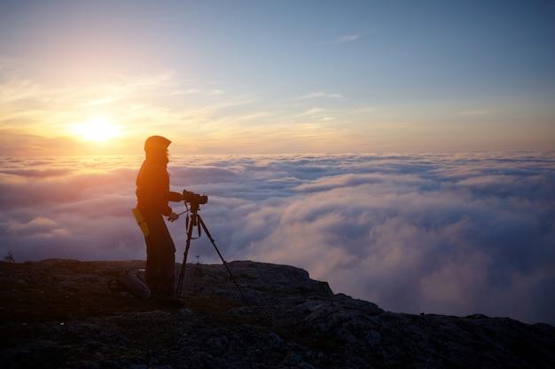 Une jeune femme faisant un film dans les montagnes brumeuses au coucher du soleil