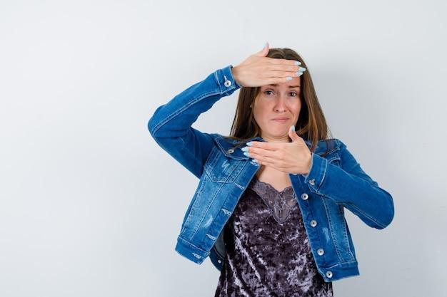Jeune femme faisant un geste de cadre en chemisier, veste en jean et l'air sérieux, vue de face.