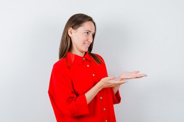 Jeune femme faisant un geste de donner ou de recevoir en blouse rouge et à la gaieté, vue de face.