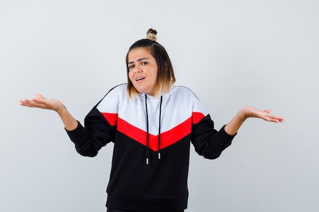 Jeune femme faisant un geste d'écailles dans un pull à capuche et l'air joyeux.