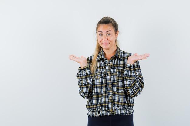 Jeune femme faisant le geste des échelles en chemise, short et à la recherche de bonne humeur. vue de face.