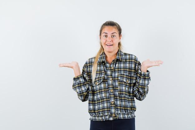 Jeune femme faisant le geste des échelles en chemise, short et à la vue de face, heureux.
