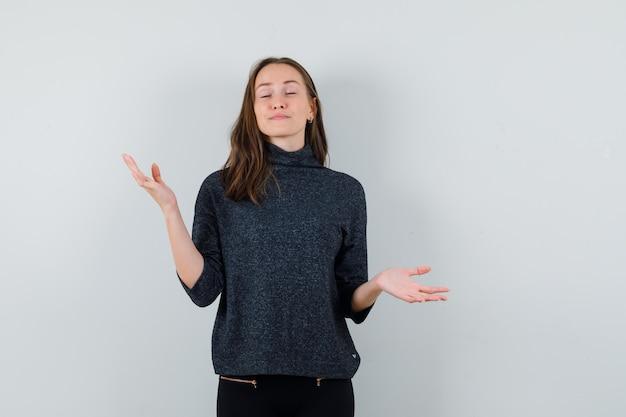 Jeune femme faisant le geste des échelles en chemise