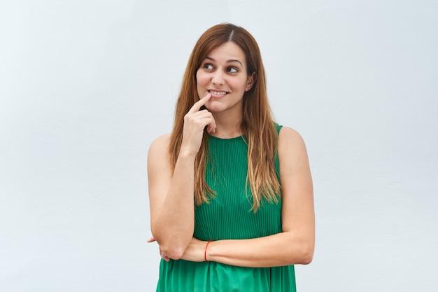 Jeune femme faisant le geste de penser isolé sur fond blanc.
