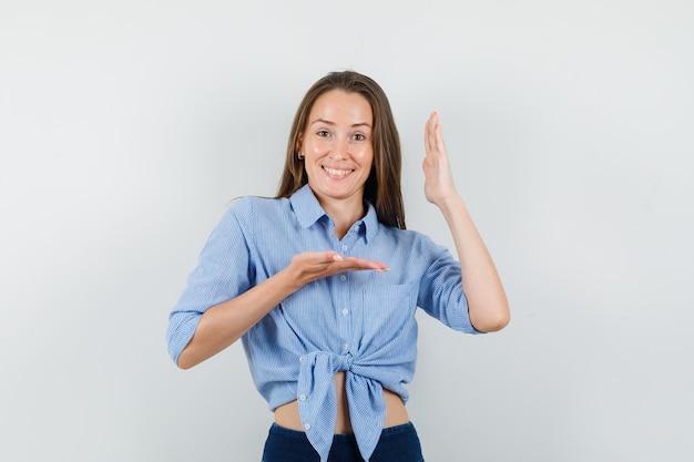 Jeune femme faisant des gestes avec les mains levées en chemise bleue, pantalon et à la joyeuse.