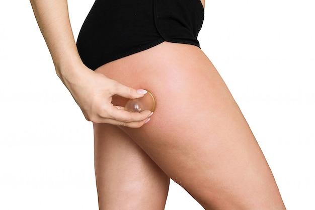 Jeune femme faisant un massage sous vide anti-cellulite sur ses hanches et ses fesses avec des pots sous vide (bocaux, banques)