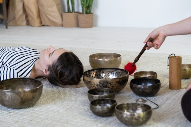 Jeune femme faisant de la massothérapie tibétaine avec des bols chantants bien-être méditation et bien-être