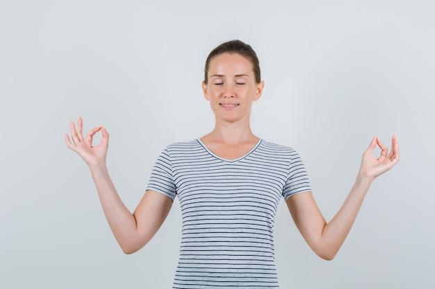 Jeune femme faisant la méditation avec les yeux fermés en t-shirt rayé et à la recherche de calme. vue de face.