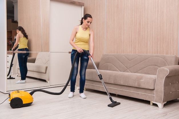 Jeune femme faisant le ménage à la maison