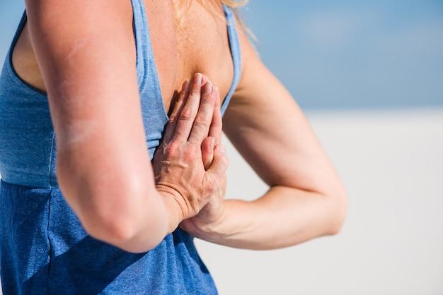 Jeune femme faisant namaste derrière le dos. fond de désert ou de sable.