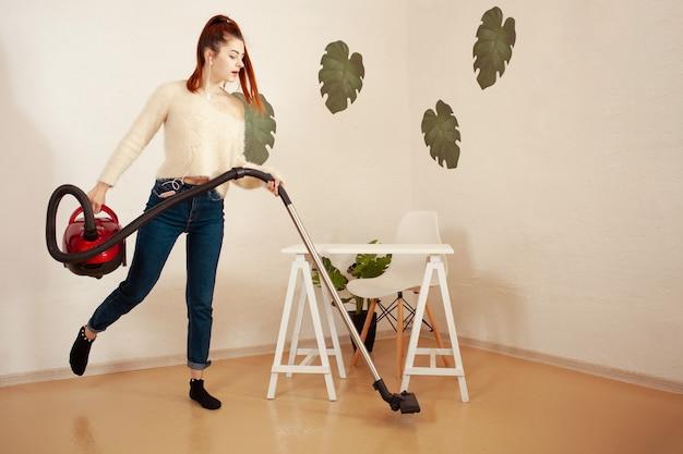 Jeune femme faisant le nettoyage dans la maison une femme aspire le sol avec un aspirateur