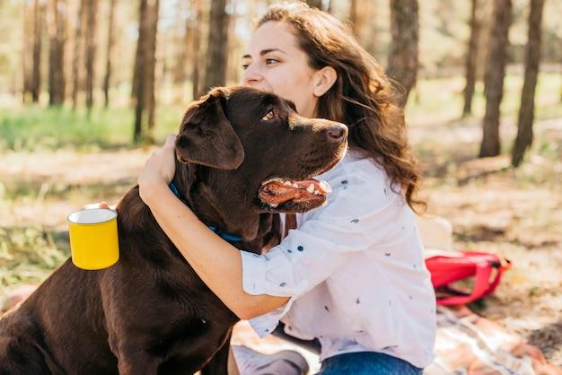 Jeune femme faisant un pique-nique avec son chien