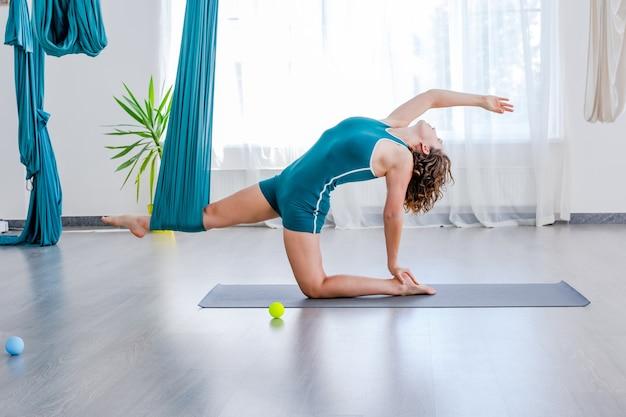Jeune femme faisant une pose d'étirement à l'aide d'un hamac en cours de gym