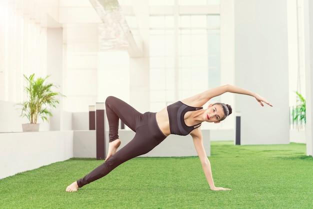 Jeune femme faisant une pose de yoga à la maison.