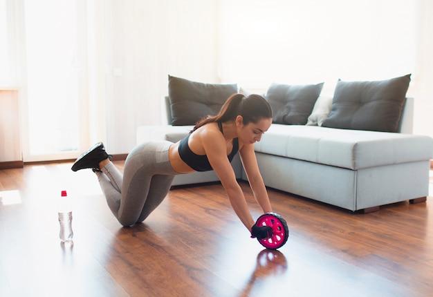 Jeune femme faisant une séance de sport dans la chambre. tenez-vous sur les genoux et utilisez un rouleau d'exercice abdominal pour les étirements corporels. formation à domicile.