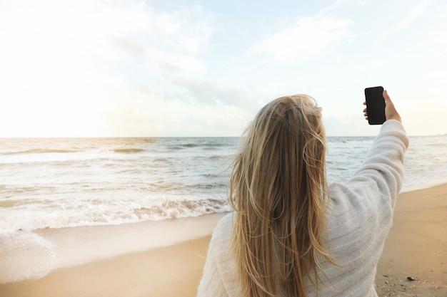 Jeune femme faisant selfie sur la plage de sable de la mer