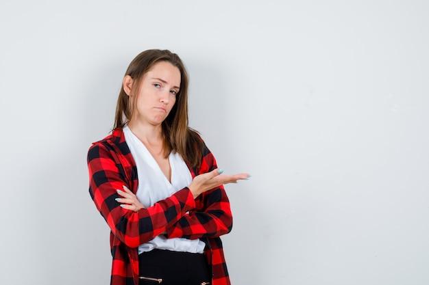 Jeune femme faisant semblant de montrer quelque chose dans des vêtements décontractés et semblant réticente, vue de face.