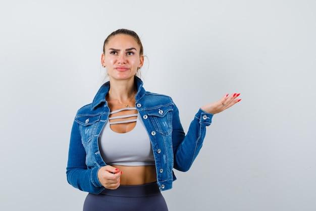 Jeune femme faisant semblant de montrer quelque chose en haut, veste en jean et semblant réfléchie, vue de face.