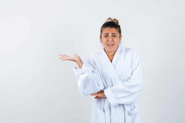 Jeune femme faisant semblant de montrer quelque chose en peignoir et à l'impuissance