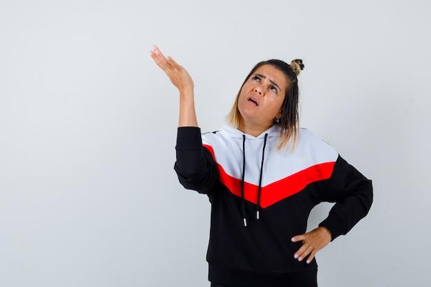 Jeune femme faisant semblant de montrer quelque chose en pull à capuche et semblant sérieuse.