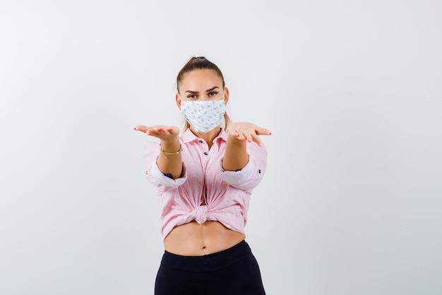 Jeune femme faisant semblant de présenter quelque chose en chemise, pantalon, masque et à la douce, vue de face.
