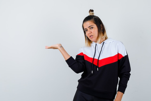 Jeune femme faisant semblant de tenir ou de montrer quelque chose dans un pull à capuche et ayant l'air confiant