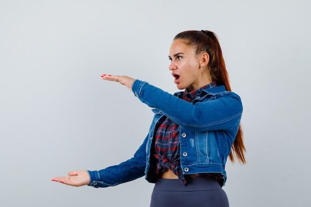 Jeune femme faisant semblant de tenir quelque chose, debout sur le côté en chemise à carreaux, veste en jean et l'air choquée.