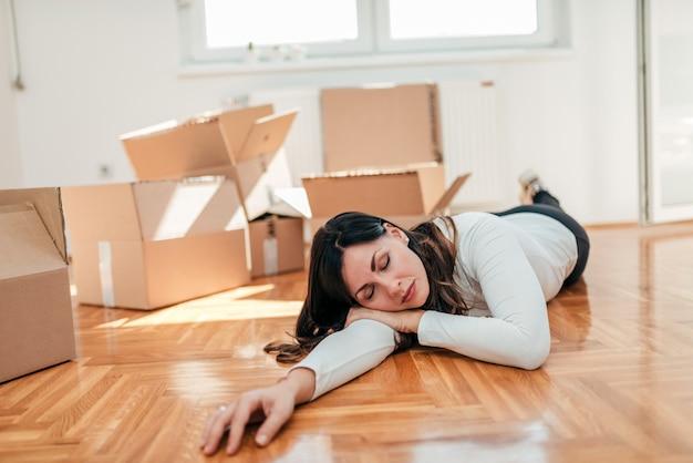 Jeune femme faisant une sieste sur le sol tout en emménageant dans une nouvelle maison.