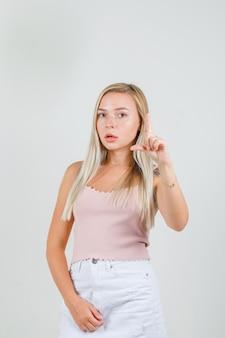 Jeune femme faisant signe de petite taille en singulet, mini jupe et à la sérieuse
