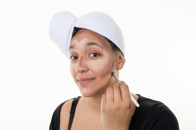 Jeune femme faisant son maquillage avec une serviette sur ses cheveux