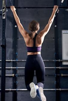 Jeune femme faisant des tractions dans la salle de gym