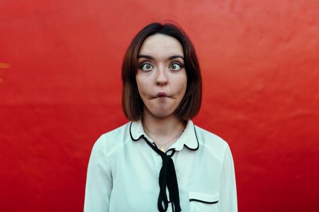Jeune femme faisant un visage de moquerie et de blague, les yeux croisés, sur un mur rouge dans la rue. jeunesse