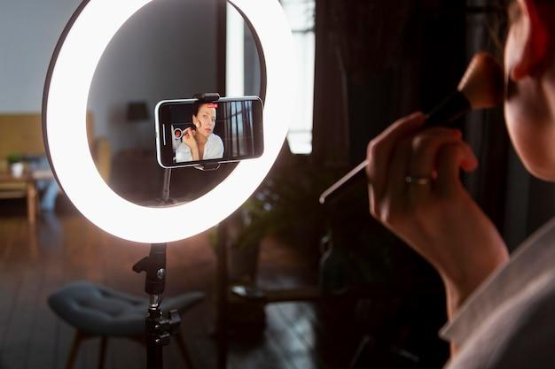 Jeune femme faisant un vlog de maquillage avec son smartphone