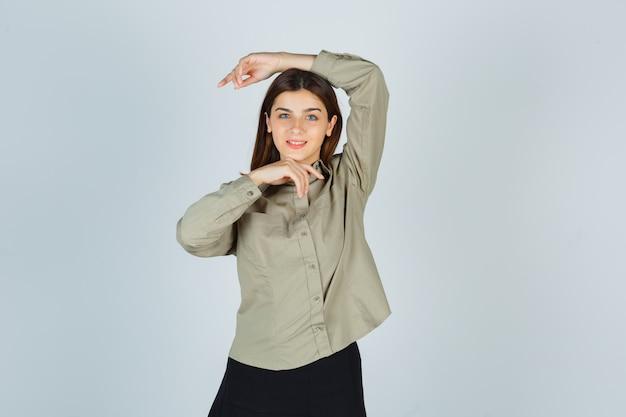 Jeune femme faisant vogue pose en chemise, jupe et à la séduisante