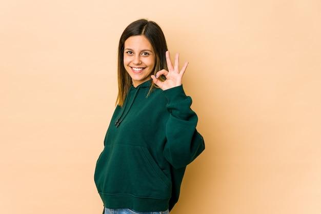Jeune femme fait un clin d'œil et tient un bon geste avec la main.