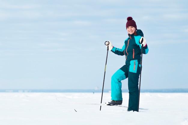 Jeune femme fait du ski en plein air au jour de neige d'hiver